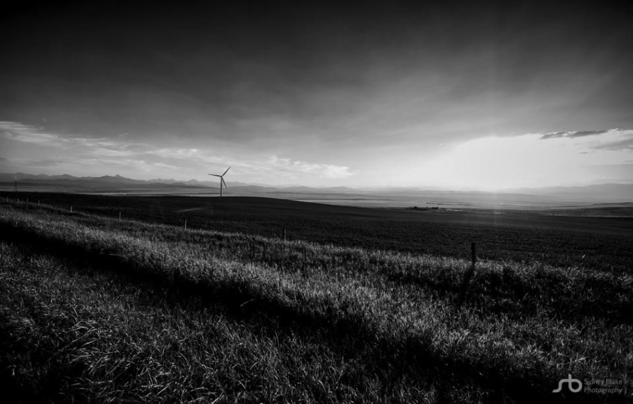 Photography vs. Life »» Sidney Blake Photography, Black and white landscape of a Pincher Creek wind turbine during a late summer sunset with a Canadian Rockies backdrop. Alberta landscape. Sidney Blake Photography